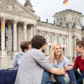 Four students sit in front of the Berlin Reichstag.